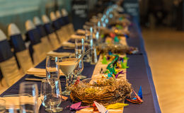 Wedding reception table. A long reception dinner table in ballroom, set with plates, glasses, decorations, chairs, and origami birds Stock Photos