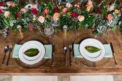 Wedding reception table setting with flower arrangements. A bride and groom`s wedding reception rustic table setting with flower arrangements stock photos