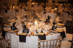 Wedding reception venue at night. A candlelit gold and black evening formal wedding reception table stock image
