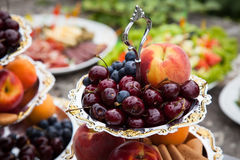 Wedding reception after wedding ceremony includes fruit, tasty,. Ripe, fresh peaches, cherries, blueberries and other snacks Stock Photo