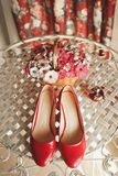 Wedding red designer bride shoes, perfume bottle and decorative flowers in a basket on the coffee table. Women`s new luxury moder. N fashion shoes made of shiny stock image