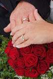 Wedding red rose bouquet and rings. Hand by hand Stock Photos