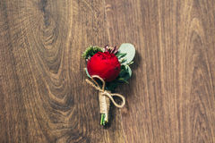 Wedding red rose boutonniere on wedding background in rustic sty Stock Photos