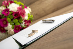 Wedding Register with Pen, Bride and Groom Rings and Bouquet of Royalty Free Stock Photo