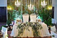 Wedding restaurant decor. Beautiful table set for green wedding or event party, indoors with big flower and candle arrangement Stock Images