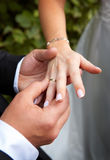 A wedding-ring. The groom inserting a ring into the bride's finger Stock Photo