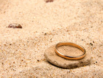 Wedding ring. Gold wedding ring on a stone in sand Royalty Free Stock Images