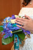 Wedding ring. Beautiful bride holding wedding ring over flowers Royalty Free Stock Photos