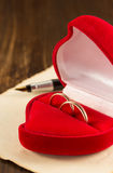 Wedding ring and aged paper on wood Royalty Free Stock Image