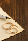 Wedding ring and aged paper on wood Stock Photos