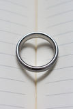 Wedding Ring Band on Book with Heart Shadow Close Up Top View. Wedding Ring Band on Book with Heart Shadow Close Up of Top View Stock Images
