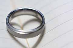Wedding Ring Band on Book with Heart Shadow Close Up Royalty Free Stock Images