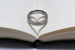 Wedding Ring Band on Book Spine with Heart Shadow. Wedding Ring Band on Book Spine with a Heart Shadow Stock Photography