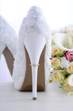 Wedding ring on beautiful white stiletto shoe heel. Stock Photography