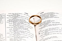 Wedding Ring on a Bible. A wedding ring on a bible open to marriage scripture Stock Image