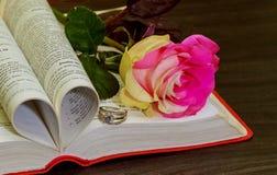 Wedding ring on the bible. Rose, wedding rings, book Royalty Free Stock Photo