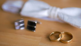 Wedding ring, bow tie and cufflinks are on the table stock video