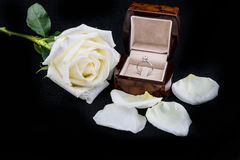 Wedding ring in box with white rose flower on black background Royalty Free Stock Photos