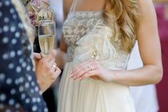 Wedding ring on bride's finger. Beautiful golden wedding ring on bride's finger Stock Photography