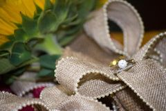 Wedding Ring on Burlap and Sun Flowers. A close up of a wedding band and diamond engagement ring on a burlap bow attached to a sunflower Royalty Free Stock Photography