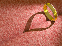 Wedding ring casting a heart on pink cloth. Background Royalty Free Stock Photo