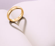 Wedding ring casting heart shaped shadow Royalty Free Stock Images