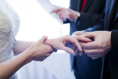 Wedding ring ceremony. Closeup of a groom putting a ring on a bride's finger during a wedding ring ceremony Royalty Free Stock Photography