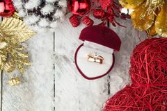 Wedding ring among Christmas decorations on wood background. Stock Image