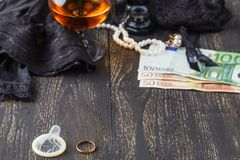 Wedding ring and condom with money on back, adultery concept Stock Photos