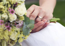 Wedding ring and flower bouquet. Detail of a ring on a hand of bride holding flower bouquet Stock Photography