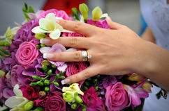 Wedding ring with flowers. A wedding ring on a finger with flowers Stock Images