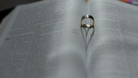 Wedding ring forming heart shape on open bible