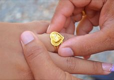 Wedding ring. Groom wearing golden ring for his bride, soft focus stock photography