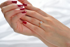 Wedding ring. On hand of bride on white cloth stock image