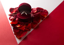 Wedding ring on a heart of rose petals corner red white backgrou Stock Photos