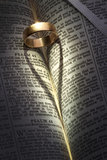 Wedding Ring - Heart Shadow. A wedding ring on an open bible casting a heart-shaped shadow Stock Photography