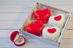 Wedding ring and heart shape cakes in box on table Royalty Free Stock Images