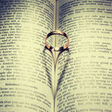 Wedding Ring and heart shaped shadow. Over a book Royalty Free Stock Photo