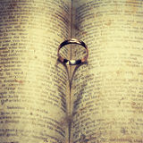 Wedding Ring and heart shaped shadow. Over a book Stock Photo