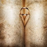 Wedding Ring and heart shaped shadow. Over a book Royalty Free Stock Images