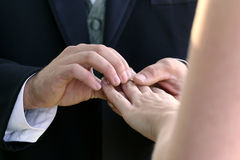 Wedding Ring for Her. Wedding ceremony moment where the groom places the wedding ring on the brides finger Stock Photo