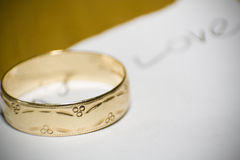 Wedding ring with love. A wedding ring on top of a sheet with the word 'Love' written on it using shallow depth of field royalty free stock photos