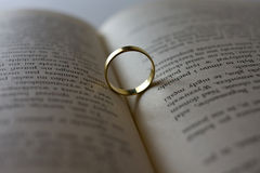 Wedding ring lying on an open book. Close up of wedding ring lying on an open book Royalty Free Stock Photos