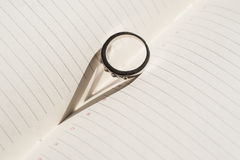 Wedding ring is on the page diary and makes a shadow in the form Royalty Free Stock Photo