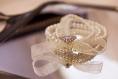 Wedding ring and a pearl bracelet Stock Photography