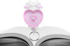 wedding ring with  pink heart-shaped clock on white Royalty Free Stock Photo