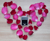 Wedding ring with pink and red rose petals in heart shape on wooden surface Royalty Free Stock Images