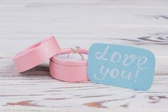 Wedding ring in present box on wooden background. Golden ring in box and card with inscription love you. Love, Valentines holiday or marriage proposal concept stock image