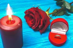 Wedding ring. The proposal. Marriage. Wedding ring in a gift present box red rose flower and burning candle on wooden table background. Marriage offer romantic stock image