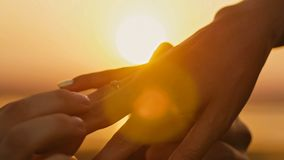 Wedding Ring Put On Finger Hands Touching Sunset Bride Groom Man Woman Marriage Proposal Vacation Honeymoon. Close up royalty free stock images